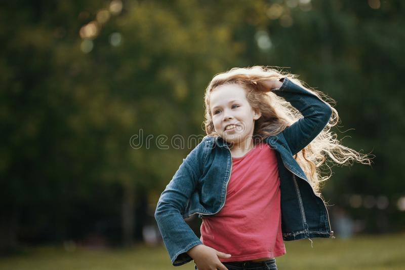 Pretty smiling child posing in park. Outdoor portrait royalty free stock photo