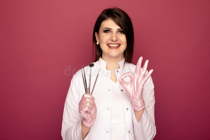 Pretty smiling dentist isolated with dentistry stuff. stock photo