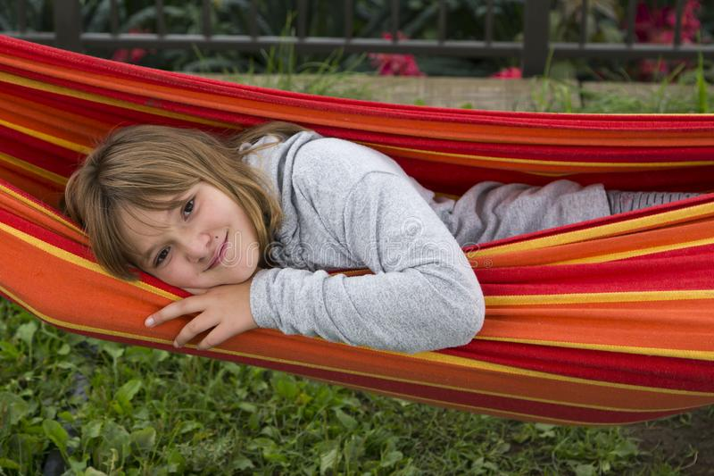 Pretty smiling fair little girl in grey sweater looking out from a colourful hammock royalty free stock photo