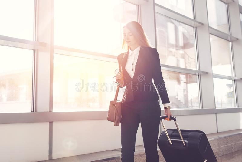 Pretty smiling female flight attendant carrying baggage going to airplane in the airport.  royalty free stock photos