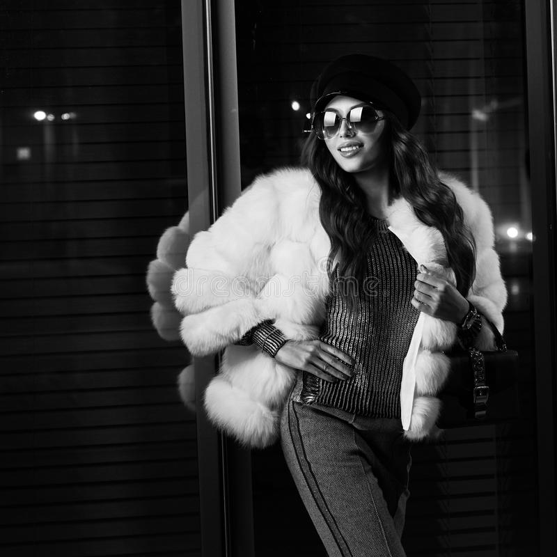 Smiling girl in trendy white fur coat and sunglasses royalty free stock photos