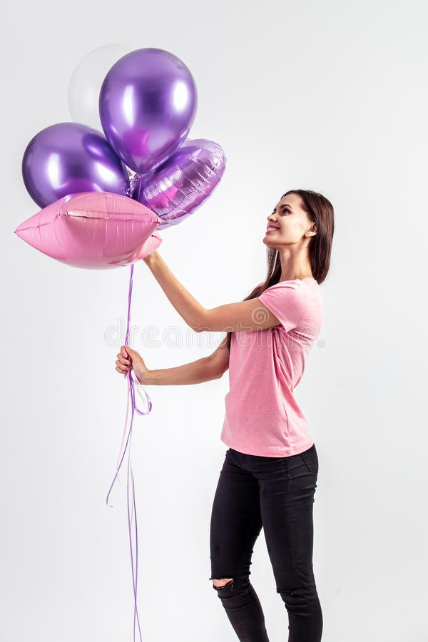 Pretty smiling girl dressed in pink t-shirt and jeans holds balloons in her hands on the white background in the studio royalty free stock photos