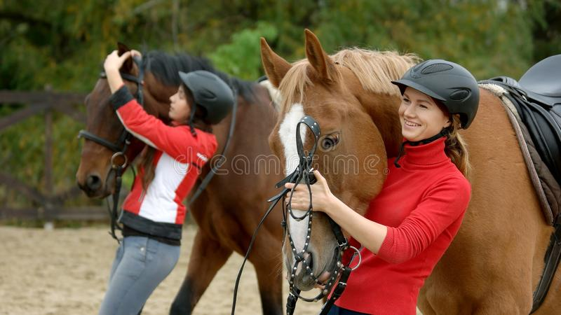 Pretty smiling girl hugging her horse at ranch. royalty free stock photography