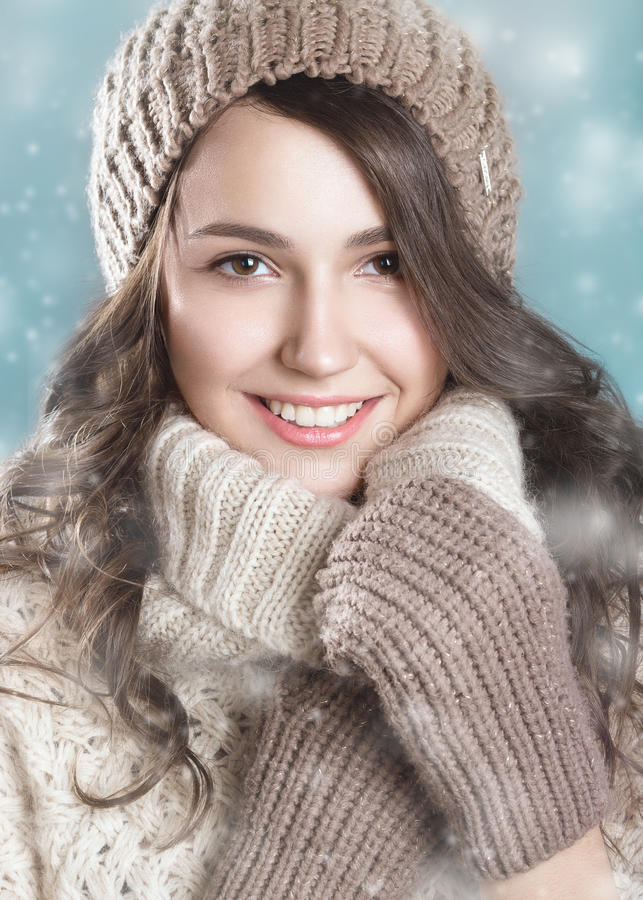 Pretty smiling girl in a knitted hat and a warm sweater. Beauty face royalty free stock photos