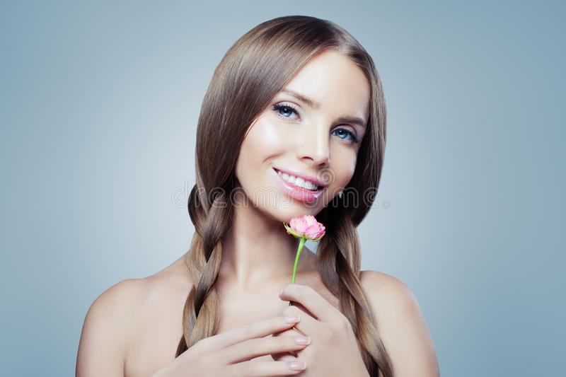 Pretty smiling girl with pink rose flower in her hands. Natural beauty royalty free stock images
