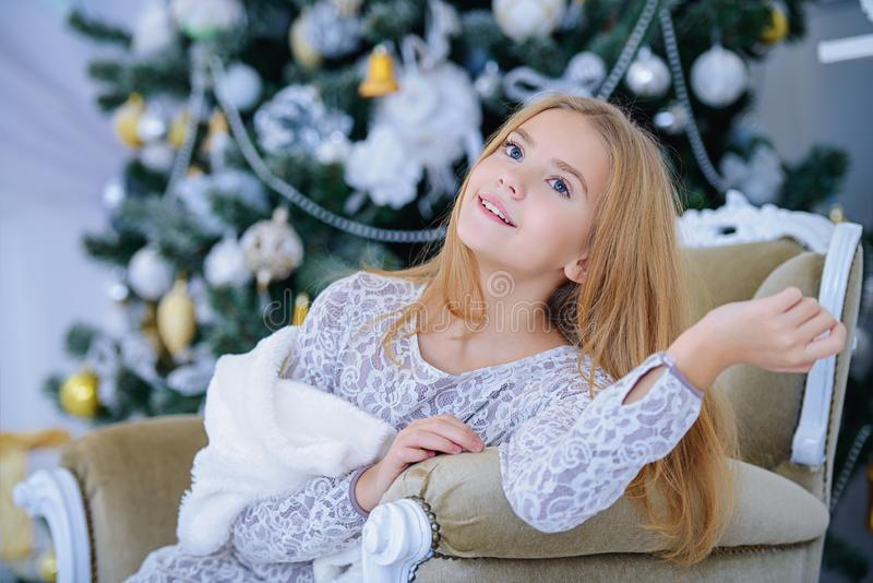 Adorable teen girl. Pretty smiling girl sitting in a armchair in a Christmas room. Merry Christmas and Happy New Year royalty free stock photography