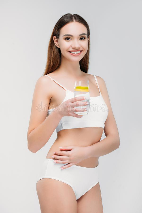 pretty smiling girl in white lingerie holding glass of water royalty free stock photo