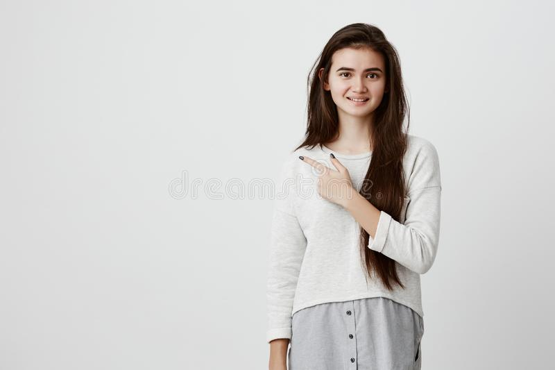 Pretty smiling joyfully female with dark long hair, pointing with her index finger away, showing copy space for royalty free stock photos