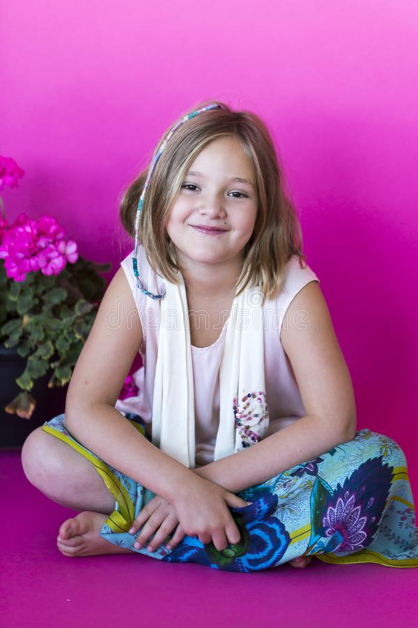 Pretty smiling little girl dressed in loose hippie-style clothes royalty free stock images