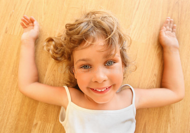 Pretty smiling little girl lies on floor stock images