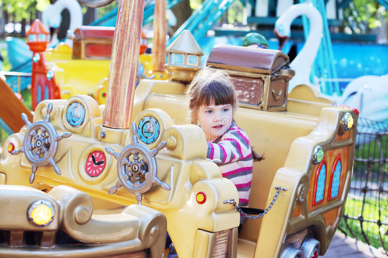 Pretty smiling little girl ride on carousel pirate ship. In summer park royalty free stock image