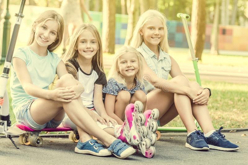 Smiling little girls sitting on the ground in the park stock photography