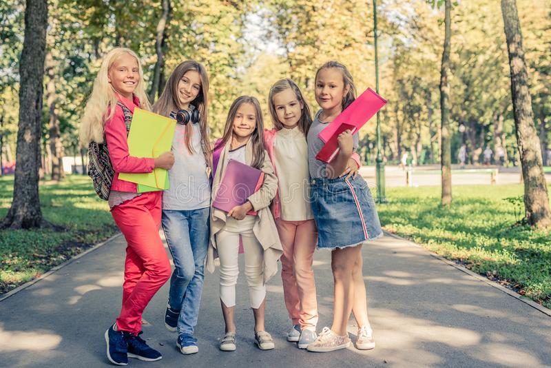 Pretty smiling little girls stand together in the sunshine park royalty free stock photos