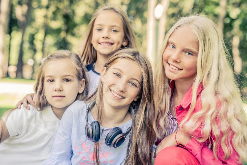 Pretty smiling little girls standing together in the park stock photo