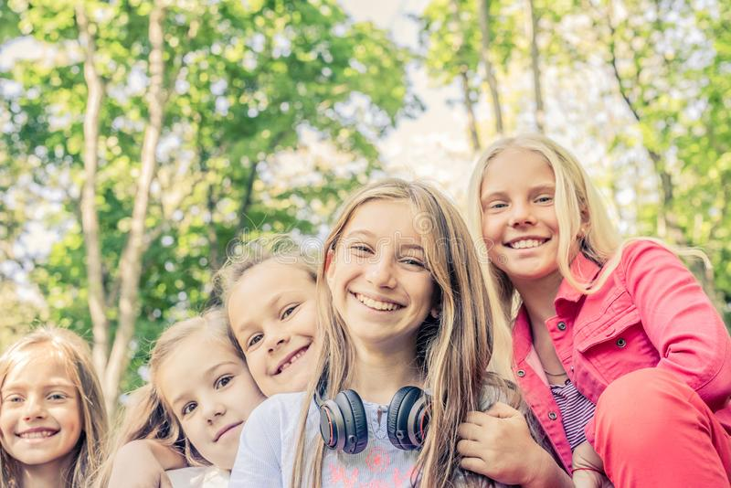 Pretty smiling little girls standing together in the park royalty free stock photos