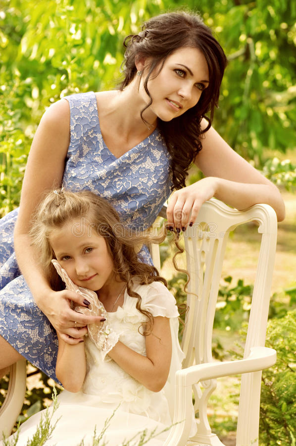 Pretty smiling mother and daughter. In green garden royalty free stock images