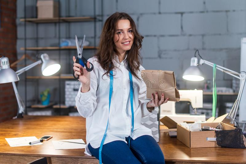 Pretty smiling seamstress sitting on table packing presents in craft paper holding scissors in modern tailor s shop.  stock photography