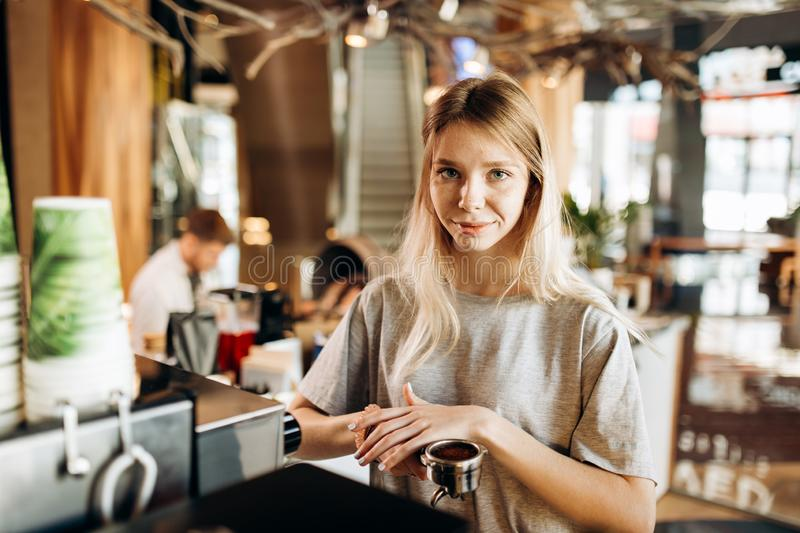 A pretty smiling slim girl,wearing casual clothes,holds some ground coffee and looks at the camera in a cozy coffee shop stock images