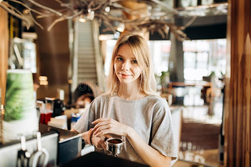 A pretty smiling slim girl,wearing casual clothes,holds some ground coffee and looks at the camera in a cozy coffee shop stock image