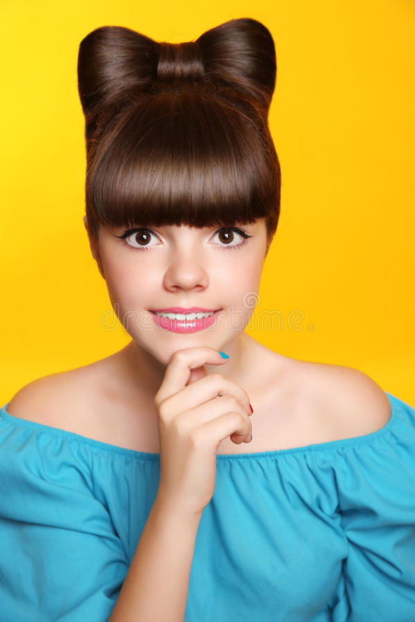 Pretty smiling teen girl with bow hairstyle, makeup and colourful manicured polish nails. Funny brunette in blue dress isolated o royalty free stock image