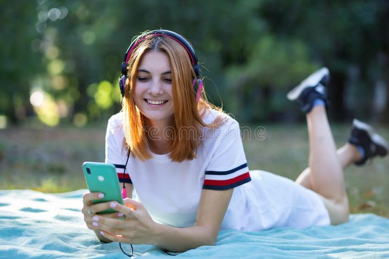 Pretty smiling teenage girl listening to music in pink earphones and using sellphone outdoors royalty free stock images