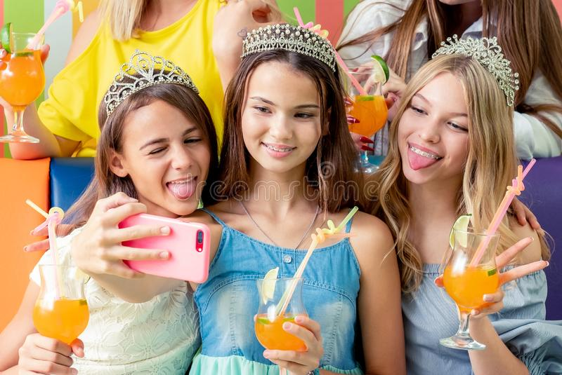 Pretty smiling teenage girls in dresses and crowns sit hugging together holding beverages royalty free stock photography
