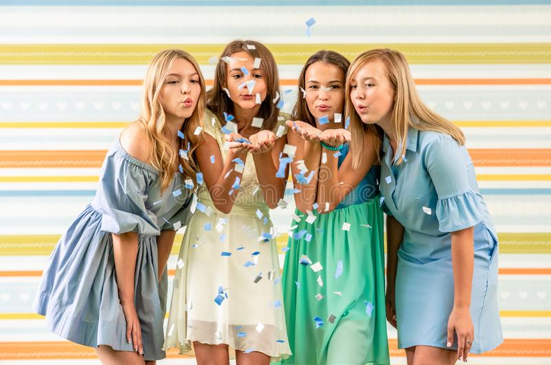 Pretty smiling teenage girls in dresses joyfully blowing confetti on birthday party stock images