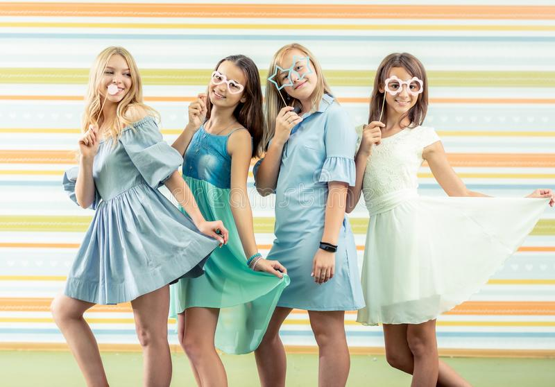 Pretty smiling teenage girls in dresses standing together and holding toy shaped glasses masks at birthday party royalty free stock photo