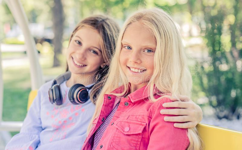 Pretty smiling teenage girls sit hugging together royalty free stock photos