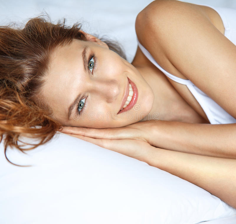 Pretty smiling woman in bed. Beautiful brunette woman lying on a pillow royalty free stock photo