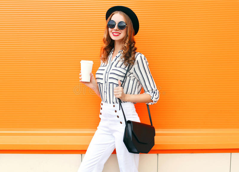 Pretty smiling woman with coffee cup wearing fashion black hat white pants handbag clutch over colorful orange. Background royalty free stock photo