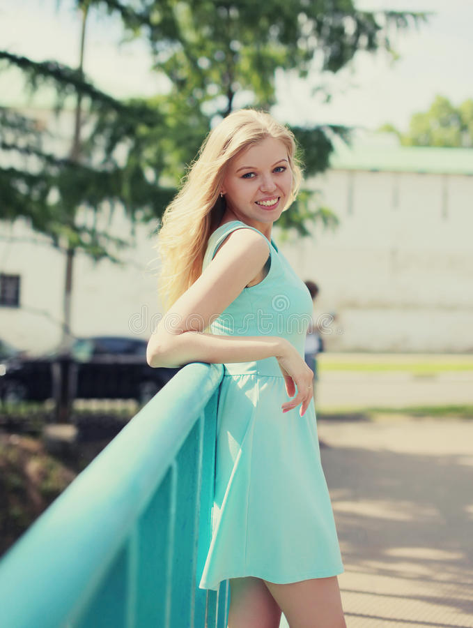 Pretty smiling woman in dress posing in the city. In the sunny day stock photos