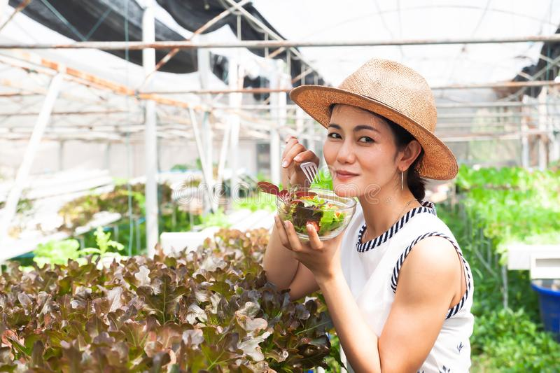 Pretty smiling woman eating fresh salad in farm. Healthy lifestyle royalty free stock photo