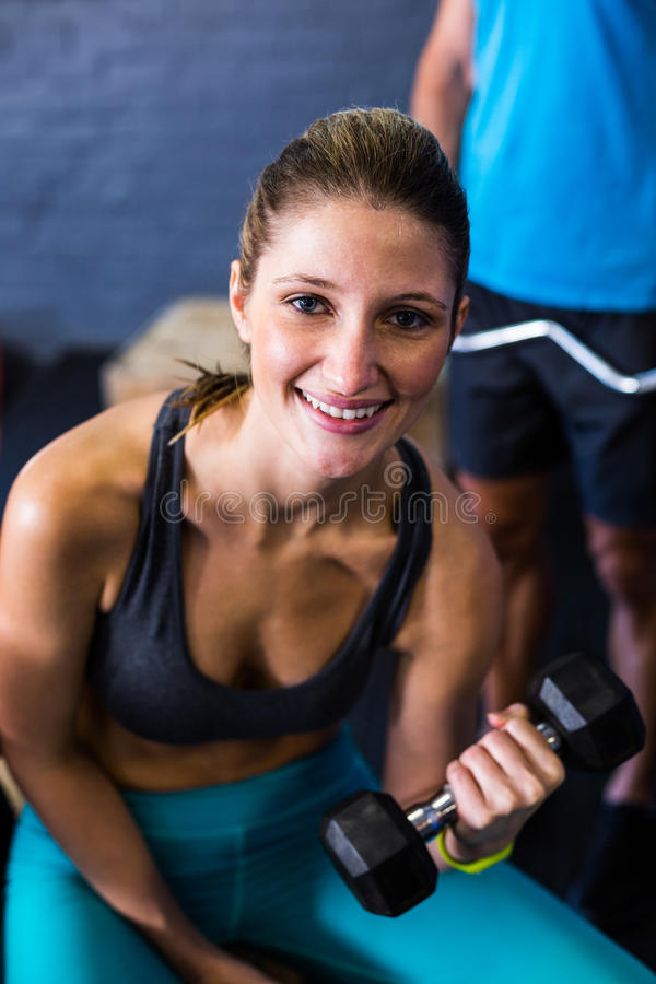 Pretty smiling woman exercising with dumbbell stock photography