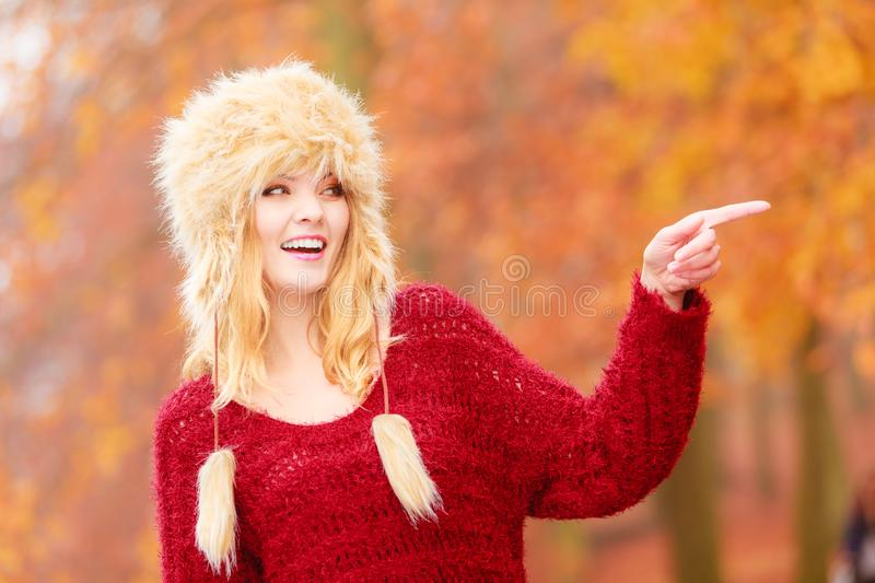 Pretty smiling woman in fur winter hat pointing stock photo