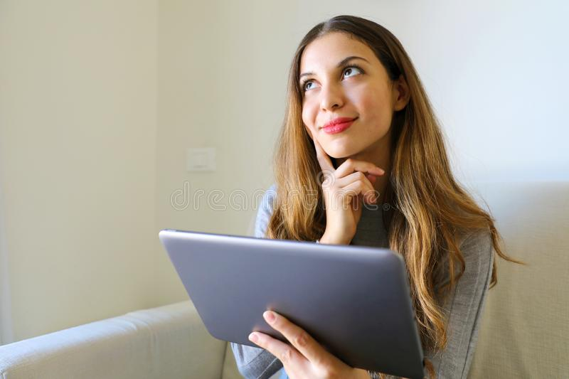 Pretty smiling woman looking up and thinking or desire holding t stock photography