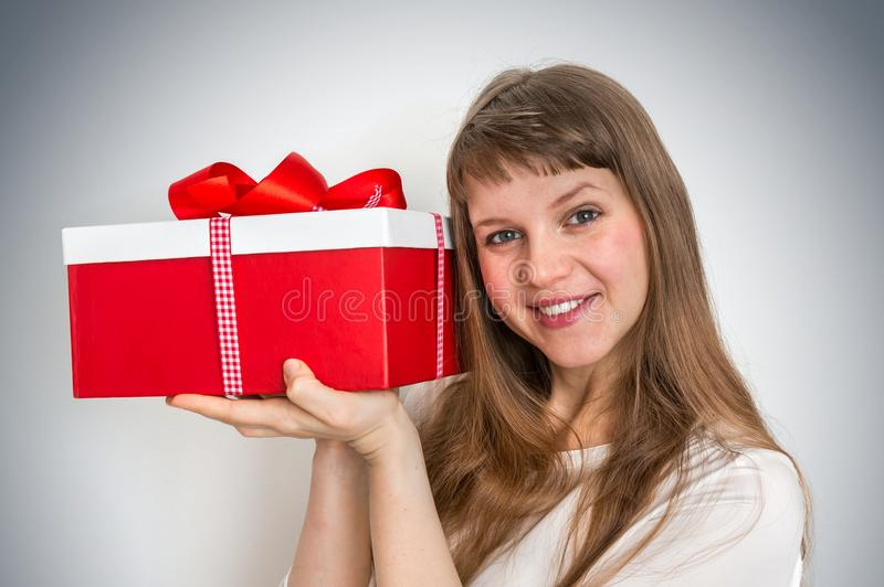 Pretty smiling woman with red gift box royalty free stock photography