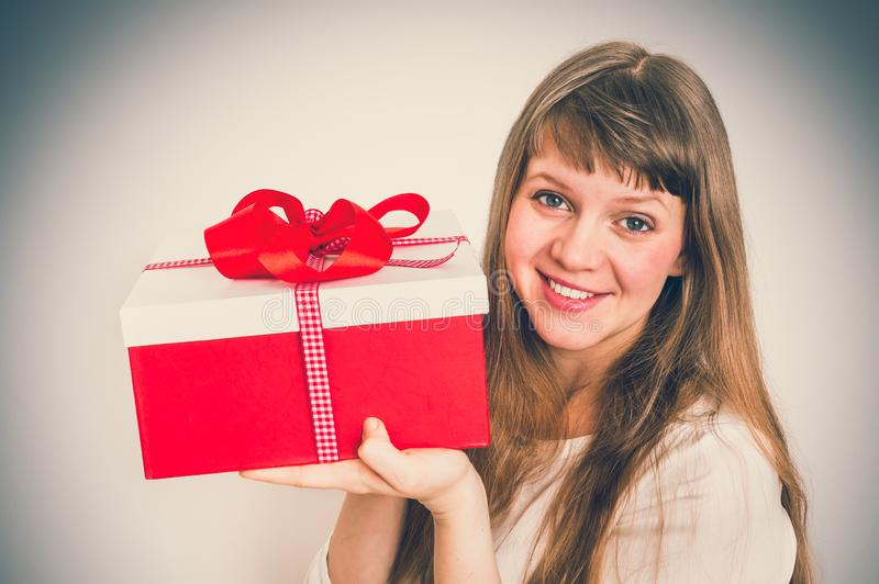 Pretty smiling woman with red gift box - retro style royalty free stock photos