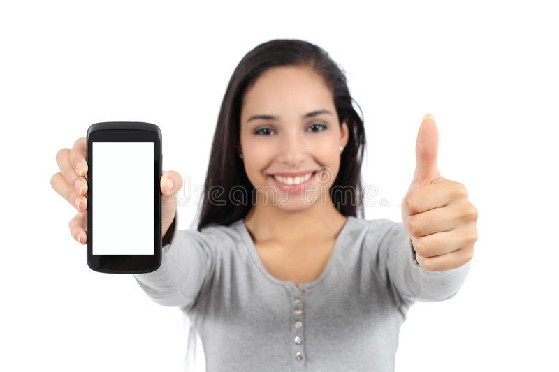 Pretty smiling woman showing a blank vertical smart phone screen and thumb up isolated. On a white background