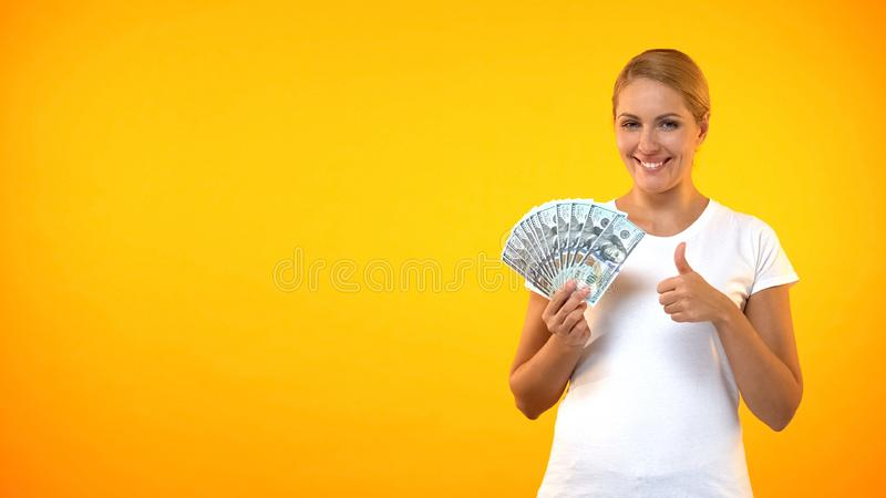 Pretty smiling woman showing thumbs up holding dollars, cashback service, credit royalty free stock image