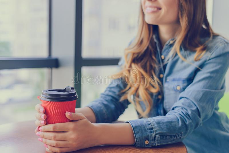 Pretty smiling woman sitting near the window in a cafe in casual clothing drinking fresh tasty coffee and having a conversation wi royalty free stock photos