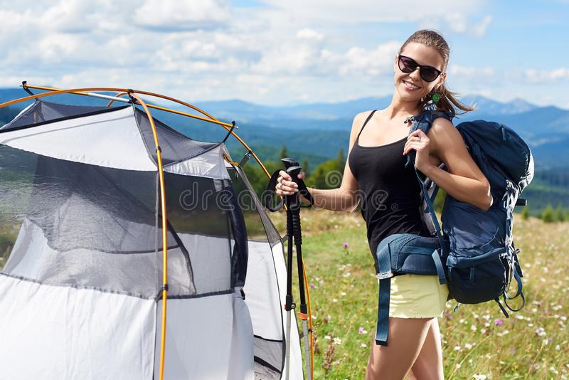 Woman tourist hiking in mountain trail, enjoying summer sunny morning in mountains near tent stock images