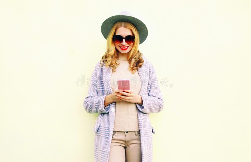 Pretty smiling woman using phone with curly hair in round hat, coat jacket royalty free stock photo