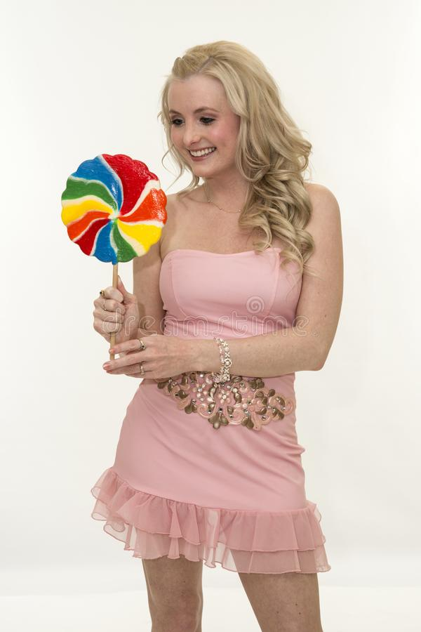 Pretty smiling young blond woman posing in studio with lollipop royalty free stock photography