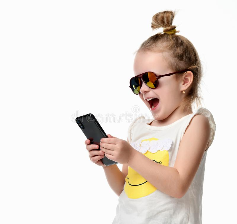 Young girl reading texting sms on the cellphone mobile with touch screen in sunglasses royalty free stock photo