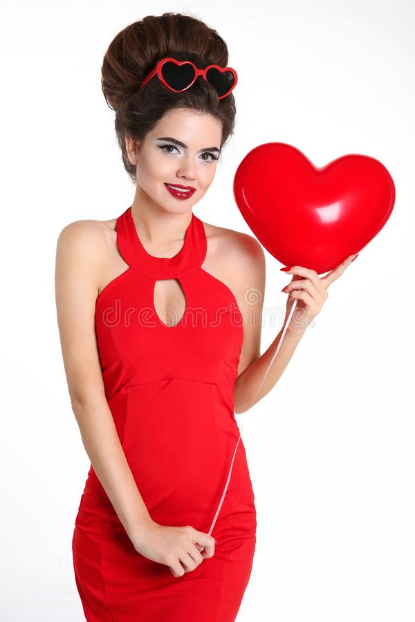 Pretty smiling young woman in red with heart balloon, brunette m stock photo