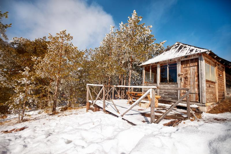 Pretty snow-covered wood cabin in winter royalty free stock photography