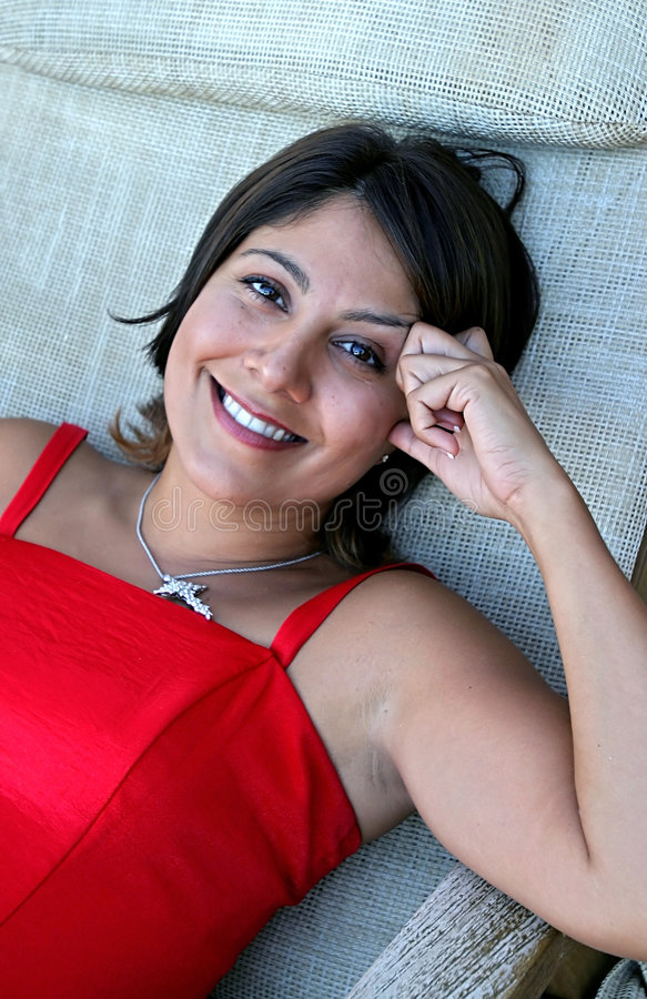 Pretty Spanish girl in red dress and diamond necklace royalty free stock photography