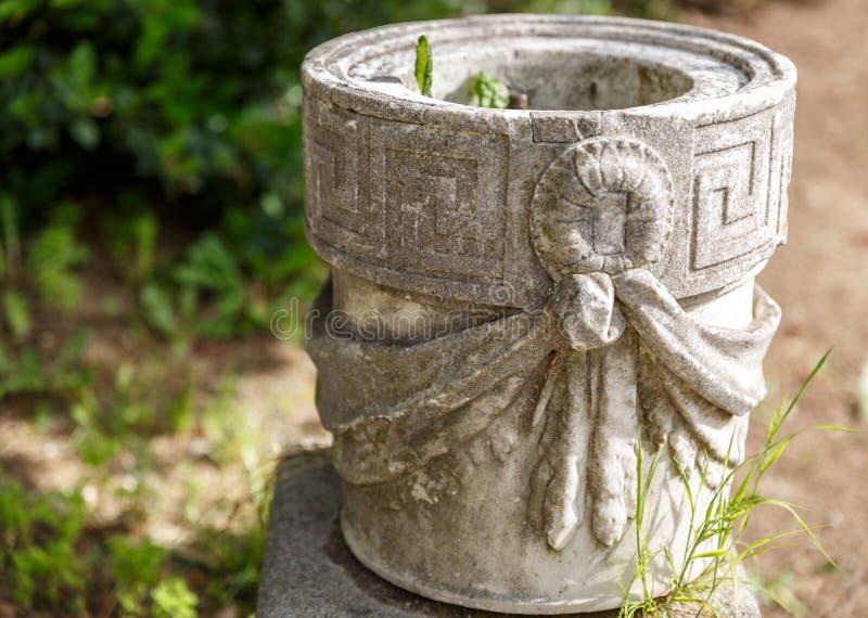 Pretty stone flowerpot in a garden. Pretty and great stone flowerpot in a garden stock photos