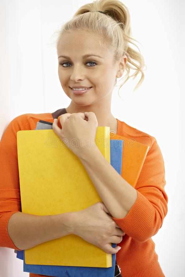 Pretty student with colorful folders smiling. Pretty female student holding colorful folders, smiling stock image